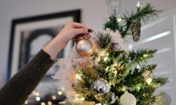 person decorating top of christmas tree