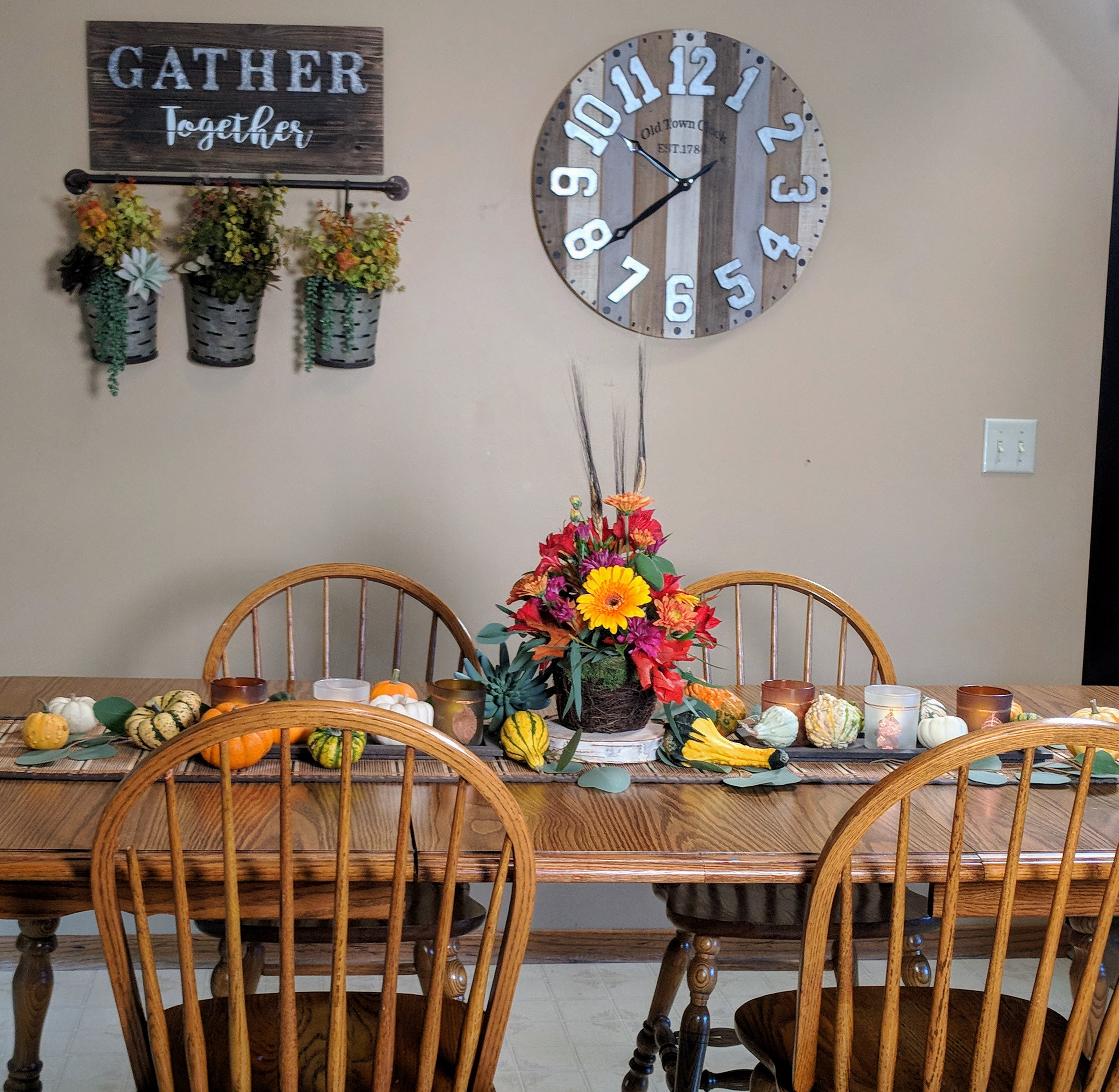 fall floral arrangement and gourds on table