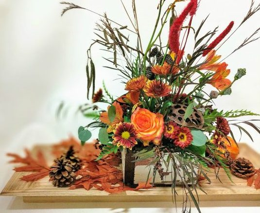 floral fall and thanksgiving arrangement with pinecones, lotus pod, carnation, rose, grasses