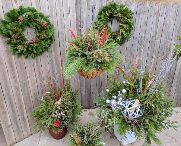 wreaths, spruce top pot, and hanging evergreen arrangement