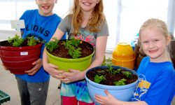 three kids with planters