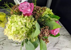 hydrangea and sedum flower arrangement with bright pink roses