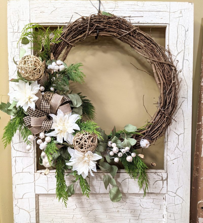 seasonal wreath with white mums, evergreens and bows